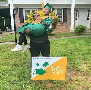 Isaiah Harris lifts his sister Alana Harris in celebration of her graduation from Parkdale High School. (Hamil R. Harris/The Washington Informer)
