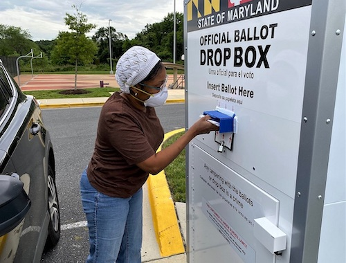 Nicole Clendenin of Bowie, Maryland, places four ballots in a drop box outside the Kentland Community Center in Landover on June 2, the day of the state's primary election. (William J. Ford/The Washington Informer)