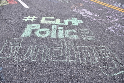 """The words """"Cut Police Funding"""" are written in chalk on a street outside the Wayne K. Curry Administration Building in Largo, Maryland, on June 15. (Anthony Tilghman/The Washington Informer)"""