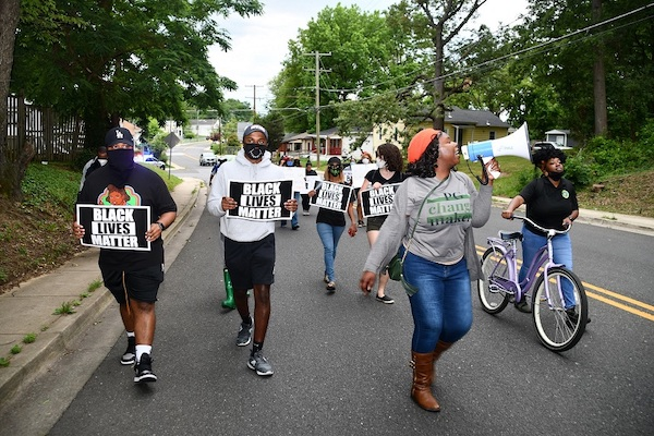 Krystal Oriadha (right) leads chants while marching through Fairmount Heights on June 22 to protest police brutality, violence against women and racism. (Anthony Tilghman/The Washington Informer)