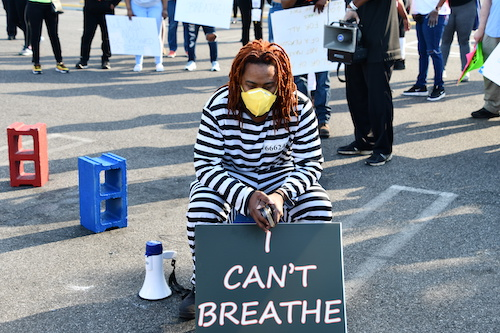 "Sherman Hardy, wearing prison garb, displays a ""I Can't Breathe"" sign during a demonstration at Eastover Shopping Center in Oxon Hill, Maryland, protesting the killing of George Floyd. (Anthony Tilghman/The Washington Informer)"