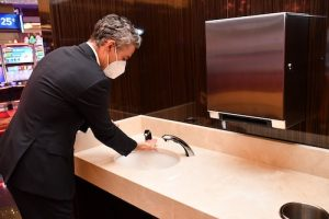 John Flynn, vice president of administration and head of health/safety strategy for MGM Resorts International, uses one of four sinks at a hand-washing station on the casino floor inside MGM National Harbor on June 25 at it prepares to reopen amid the coronavirus pandemic. (Anthony Tilghman/The Washington Informer)