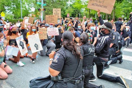 Police officers from the Montgomery County's 2nd District take a knee with protestors during a peaceful protest in Bethesda, Maryland, on June 2 against racism and police brutality. (Brigette Squire/The Washington Informer)