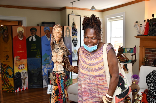 "Juanita ""Busy Bee"" Britton poses in her home filled with beautiful art and craft pieces. (Anthony Tilghman/The Washington Informer)"