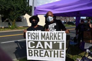 "Joseph ""OT Kanye"" Tolbert III, who helped organize a protest against The Fish Market, stands with a demonstrator at the restaurant in Clinton, Maryland, on June 29. (Anthony Tilghman/The Washington Informer)"