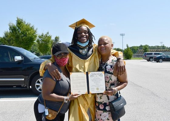 Julian Murdock, who graduated from Oxon Hill High School, stands between his godmother Althea Stephenson (left) and his mother Maureen Telfer after a diploma ceremony on Aug. 5. Murdock will attend Prince George's Community College. (Anthony Tilghman/The Washington Informer)