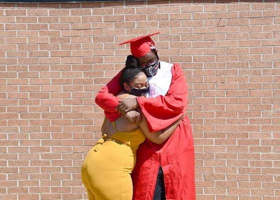Krystopher Howard (right) hugs his sister Claudia Howard after he received his high school diploma during a ceremony at Suitland High School on Aug. 5. Howard will attend Prince George's Community College. (Anthony Tilghman/The Washington Informer)