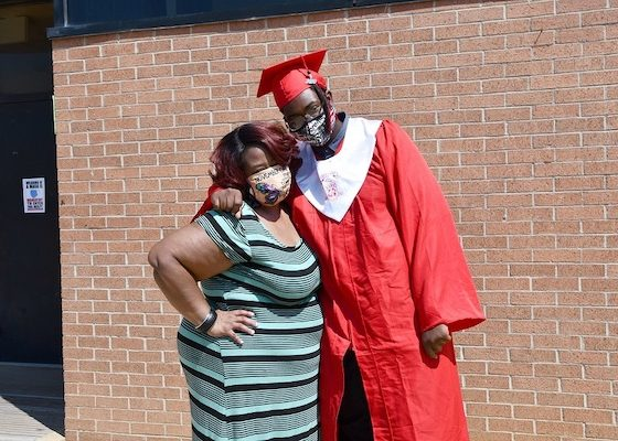 Krystopher Howard (right) hugs his mother Kenyetta Howard after he received his high school diploma during a ceremony at Suitland High School on Aug. 5. Howard will attend Prince George's Community College. (Anthony Tilghman/The Washington Informer)