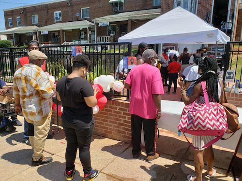 Local residents crowd the entrance of Janae Coleman's new restaurant during her food giveaway for COVID-19 relief.