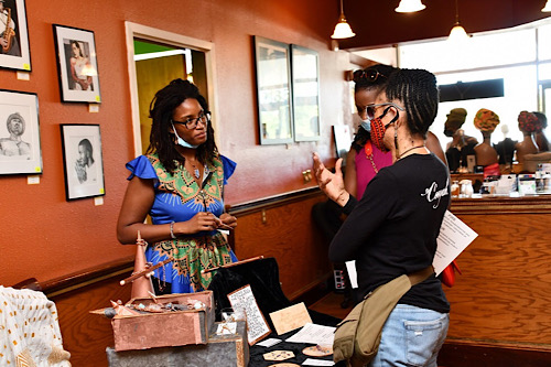Lark Dixon (left), owner of Finding All the Chakras, listens to customers during Black Wall Street Renaissance at Everlasting Life Restaurant in Capitol Heights, Maryland, on Sept. 5. (Anthony Tilghman/The Washington Informer)
