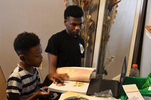 James Johnson, a 10th grader at a public charter school, helps his younger brother Asahai do his virtual classwork.  (Roy Lewis/The Washington Informer)
