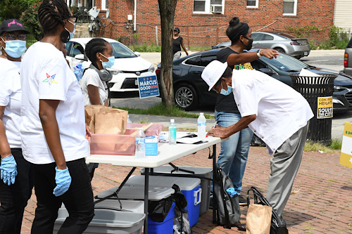 Volunteers help register a Ward 8 resident to vote. (Roy Lewis/The Washington Informer)