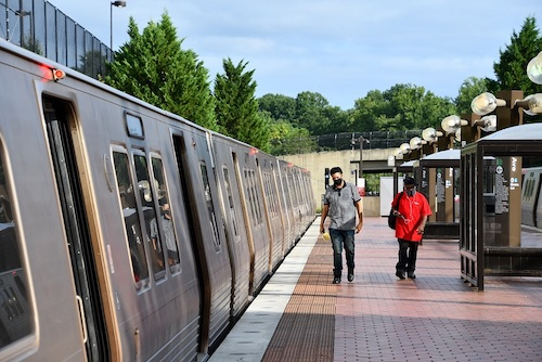 Riders prepare to board a Green Line train at the Branch Avenue Metro station. (Anthony Tilghman/The Washington Informer)