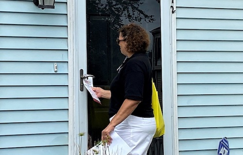 Nikki Greco, constituent services director for Prince George's County Council member Jolene Ivey, prepares to place a census door hanger on a townhouse in Landover on Sept. 12. (William J. Ford/The Washington Informer)