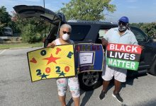 Marion Jamison (left) holds signs she created for a caravan with the First Baptist Church of Highland Park to bring attention to the lives lost to police and encourage people to participate in the census. (Hamil R. Harris/The Washington Informer)