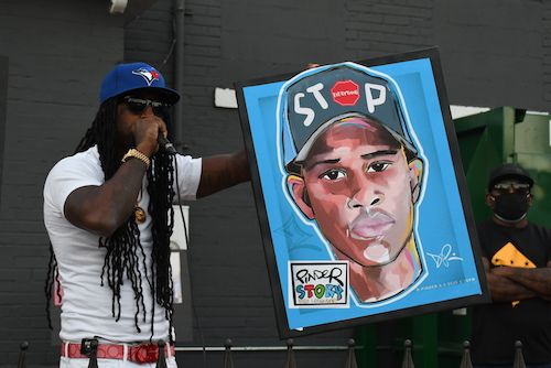 Mike D'Angelo, an anti-violence activist and uncle of the late Mikayah Wilson, speaks during a candlelight vigil for Deon Kay on Sept. 5, where he presented a painting by Demont Pinder of the late Kay. (Roy Lewis/The Washington Informer)