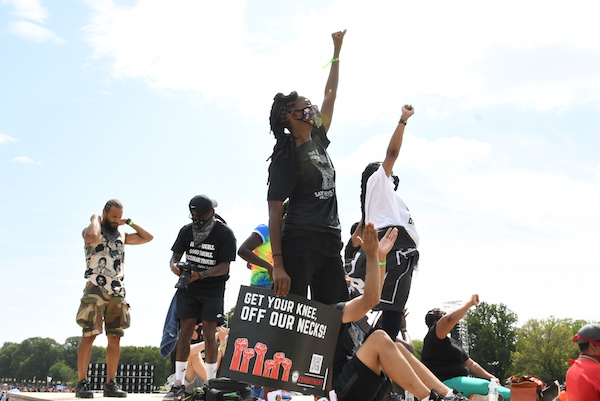 Protesters stand atop a stoop at the Lincoln Memorial in Washington with raised fists during the Commitment March on Aug. 28. (Roy Lewis/The Washington Informer)