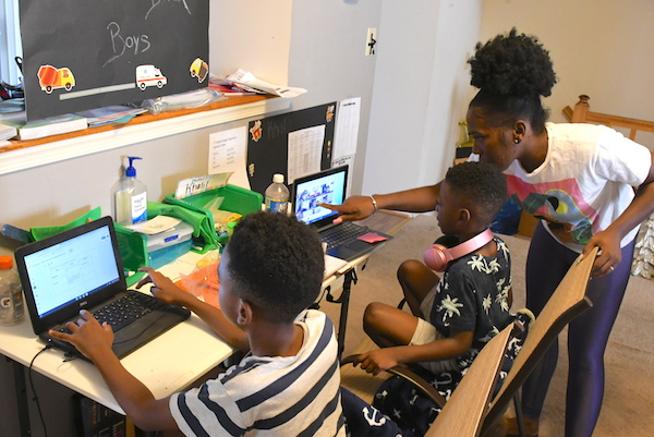 Angel Johnson, 33, helps her two elementary school aged sons, Asahai and Khalil, with schoolwork during their virtual learning class work. (Roy Lewis/The Washington Informer)