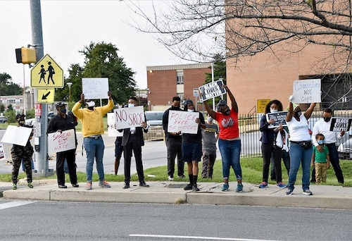 Protesters hold signs during a Sept. 15 rally outside Suitland High School in Forestville, Maryland, against school resource officers in Prince George's County schools. (Anthony Tilghman/The Washington Informer)