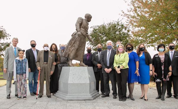 Community members and local dignitaries attend an Oct. 24 event at Jennie Dean Elementary School in Manassas, Virginia, to unveil a statue dedicated to the school's namesake. From left: Manassas Mayor Harry J. Parrish II, Aaliya Critzer, Council Member Mark Wolfe, Carroll Braxton and daughter Monique Braxton, Marshall Sprow, Council Member Ralph Smith, Council Member Ian Lovejoy, Kevin and Barbara Hutto, Council Member Michelle Davis-Younger, Council Member Pam Sebesky, Council Member Theresa Coates Ellis, City Manager Pat Pate. (Courtesy of FBC Manassas)