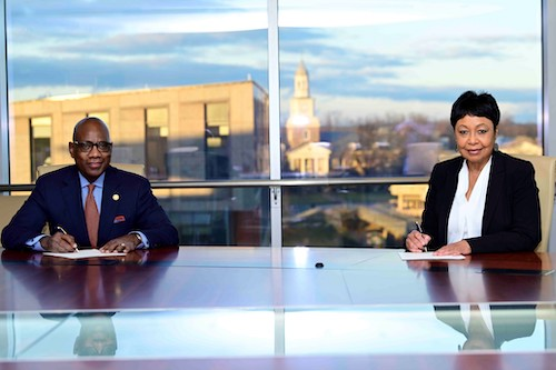 Morgan State University President David Wilson and Vice President of Institutional Advancement Donna Howard participate in a ceremonial signing of a $40 million gift from author Mackenzie Scott. (Courtesy of Morgan State University)