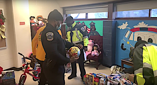 Officers from the Metropolitan Police Department's 7th District distribute toys to children at the Trinity Shelter in southeast D.C. on Dec. 21.