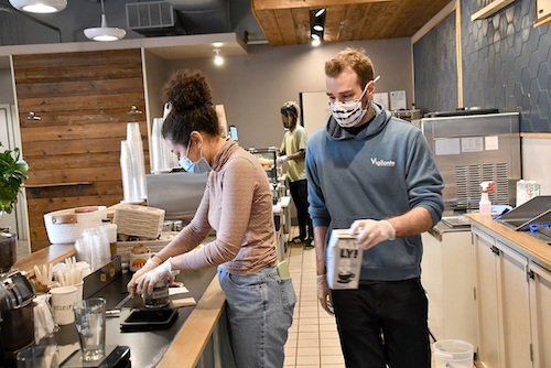 Taylor Smith (left) and Nick Balmadier are two of the employees at Vigilante Coffee Co. in College Park, Maryland. The coffee shop has a bigger operation at its Hyattsville location. (Anthony Tilghman/The Washington Informer)