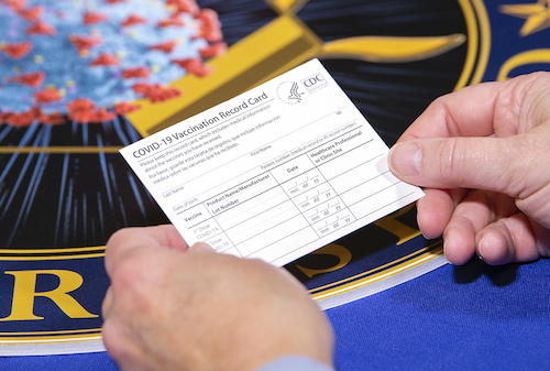 A Department of Health and Human Services employee holds a COVID-19 vaccine record card. The cards will be sent out as part of vaccination kits from Operation Warp Speed, which is an effort by several U.S. government components and public partnerships to facilitate the development, manufacturing and distribution of COVID-19 vaccines, therapeutics and diagnostics. (DoD photo by EJ Hersom)