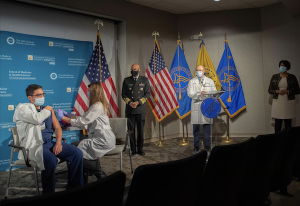 U.S. Surgeon General Jerome Adams (far right) watches as a doctor at George Washington University Hospital is administered the first COVID-19 vaccine in the Washington, D.C., area. (Courtesy of Office of the Mayor of the District of Columbia)