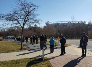 People stand in line outside the Wayne K. Curry Sports and Learning Complex in Landover, Maryland, to receive a coronavirus vaccine on Jan. 25. (Anthony Tilghman/The Washington Informer)
