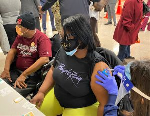 Angela Stewart, sitting next to her father Robert Gaskin, receives a dose of coronavirus vaccine at a vaccination clinic at Reid Temple AME Church in Glenn Dale, Maryland, on Feb. 12. (William J. Ford/The Washington Informer)