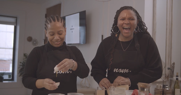 Tyler Davis (left), founder of NOM, and Simone Clark share a laugh while participating in an in-person cooking class. (Courtesy of Owen Hart)