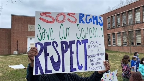 A man holds a sign in protest of shipping Robert Goddard Montessori students to another building. (William J. Ford/The Washington Informer)