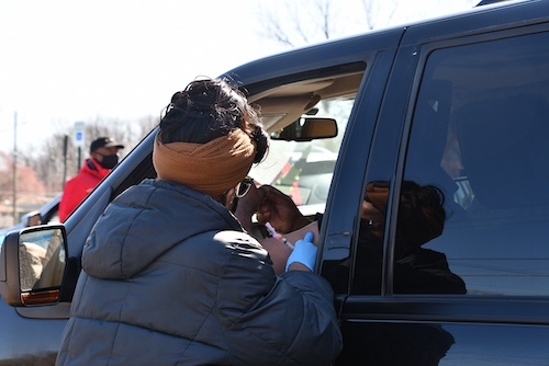 A District Heights, Maryland, resident sitting inside a vehicle prepares to receive a coronavirus vaccine during a drive-thru community clinic outside First Baptist Church of District Heights on March 20. (Anthony Tilghman/The Washington Informer)