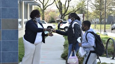 **FILE** Tulip Grove Elementary Principal Jaime Coffen squirts hand sanitizer into the hand of a student on April 8, the first day of hybrid learning in Prince George's County. (Robert R. Roberts/The Washington Informer)