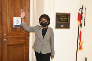 Rep. Maxine Waters (D-Calif.) signals support for D.C. statehood on April 22 as she prepares to walk from her office to the U.S. Capitol to vote on related legislation. (Roy Lewis/The Washington Informer)