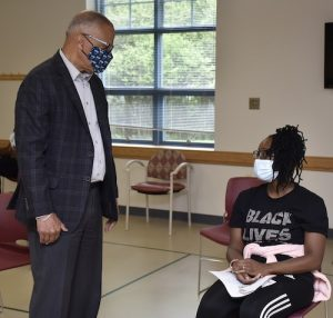 Maryland Lt. Gov. Boyd Rutherford (left) chats with Yinka Philemon of Bowie, Maryland, in the waiting area after she received a dose of the Pfizer coronavirus vaccine at the Bowie Senior Center on April 21. (Robert R. Roberts/The Washington Informer)