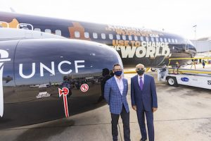 Alaska Airlines CEO Ben Minicucci and UNCF Executive Vice President Maurice Jenkins celebrate their partnership and the inaugural flight of the airline's newest edition. (Brigette Squire/The Washington Informer)