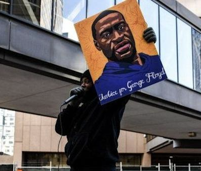 A protester stands outside the courthouse where the trial of the ex-Minneapolis police officer accused of killing George Floyd is taking place. (Courtesy photo)