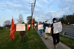 Demonstrators march along Greenbelt Road near Eleanor Roosevelt High School on April 7 to protest Prince George's County Public Schools restarting in-person instruction the following day. (Anthony Tilghman/The Washington Informer)