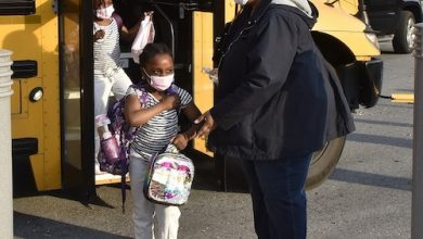 Students at Tulip Grove Elementary in Bowie exit a school bus on April 8, the first day of hybrid learning in Prince George's County. (Robert R. Roberts/The Washington Informer)