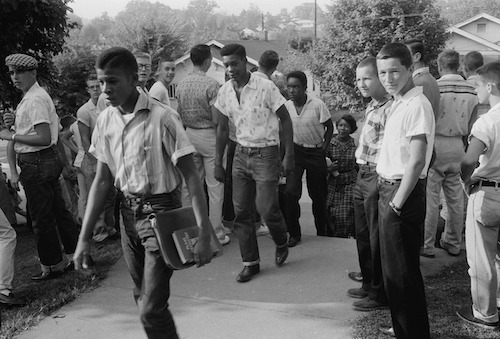**FILE** A line of African American boys walk through a crowd of white boys during a period of violence related to school integration. (Library of Congress via Wikimedia Commons)