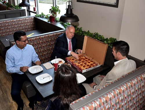 Maryland Gov. Larry Hogan cuts a slice of pepperoni pizza at Ledo Pizza in Oxon Hill, Maryland, while visiting to promote the restaurant's coronavirus vaccine initiative on May 13. Seated with with the governor are (from left) franchise owner Moe Uddin and his wife Merina Sultana, and James Beall, president of Ledo Pizza. (Robert R. Roberts/The Washington Informer)