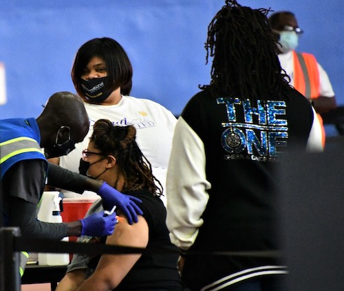 Jamara Bell, 17, receives a Pfizer-BioNTech coronavirus vaccine May 14 during a vaccine-a-thon event at the Wayne K. Curry Sports and Learning Center in Landover, Maryland. (Anthony Tilghman/The Washington Informer)