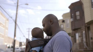 """Filmmaker Khalil Munir holds his son in Philadelphia in a scene from the film """"What's in a Name?"""" one of the winners in the PitchBLACK Awards. (Courtesy of Kuyamba Media)"""