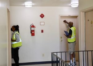 Two members of a Prince George's County COVID-19 vaccine outreach team knock on doors at Southview Apartments in Oxon Hill, Maryland, on June 16 to encourage residents to receive a vaccine. (Anthony Tilghman/The Washington Informer)