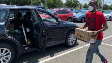 The Rev. Tony Lee, pastor of Community of Hope AME Church, carries a box of produce to place inside a vehicle during a food giveaway in the parking lot of Forman Mills in Hillcrest Heights, Maryland, on June 21. (William J. Ford/The Washington Informer)