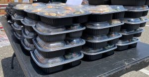 Dozens of meals sit on a table waiting to be distributed to residents during a food giveaway in Hillcrest Heights, Maryland, on June 21. (William J. Ford/The Washington Informer)