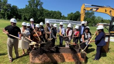 Marcus Bryant (center in yellow tie) joins state, county, school and construction officials tossing dirt at a June 28 groundbreaking ceremony for a new Walker Mill Middle School in Capitol Heights, Maryland. (William J. Ford/The Washington Informer)