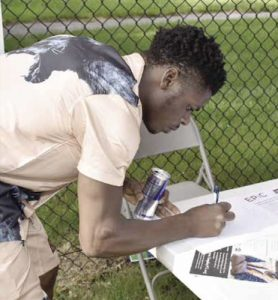 """Devin Rice, 24, jots down his contact information at an """"Our Streets, Our Future"""" event in District Heights on June 25. (Robert R. Roberts/The Washington Informer)"""